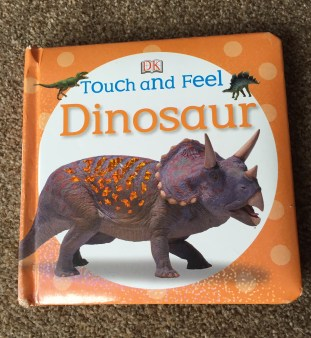 The front cover of the DK Touch and Feel Dinosaur book with a photo style image of a dinosaur with horns as the main image and two smaller dinosaurs around the title. the background is orange and dotty with a large white circle in the centre where the title and main picture are.