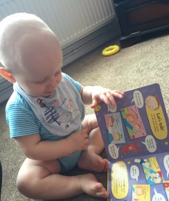 Almost bald, blond 8 month old baby in a blue stripe vest and a blue bib is sat on a beige carpet holding an open book, where you can see lots of pictures and speech bubbles
