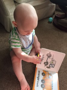 almost bald, blond 8 month old wearing a white vest with crocodiles on it sitting on a beige carpet with his hands on a book where you can see a white car and an orange truck illustrated