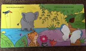 Open book showing illustrations of an elephant in water, a yellow background, lots of trees and plants, a tiger, and a butterfly with silver shiny material as it's wings