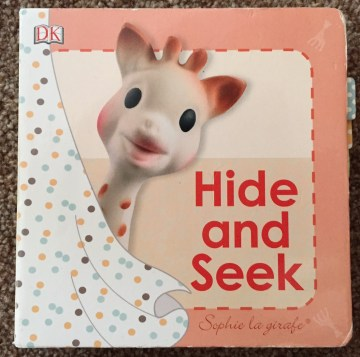 Front cover of Hide and Seek Sophie la girafe book - red writing on a pale orange background with a toy Sophie the Giraffe peeking around a dotty shower curtain