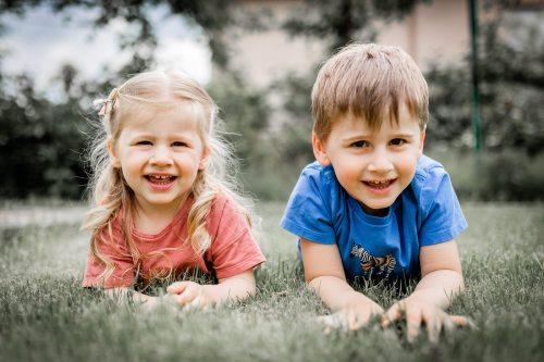 Enfants souriants couchés dans l'herbe