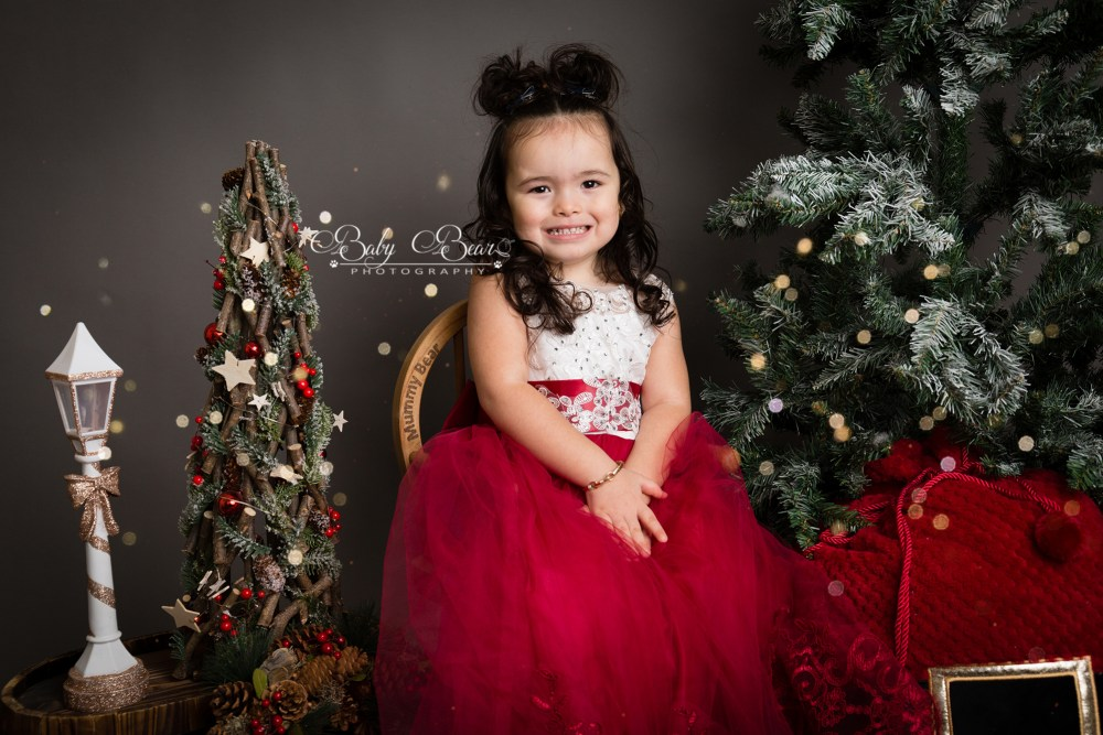 Girl smiling by christmas trees