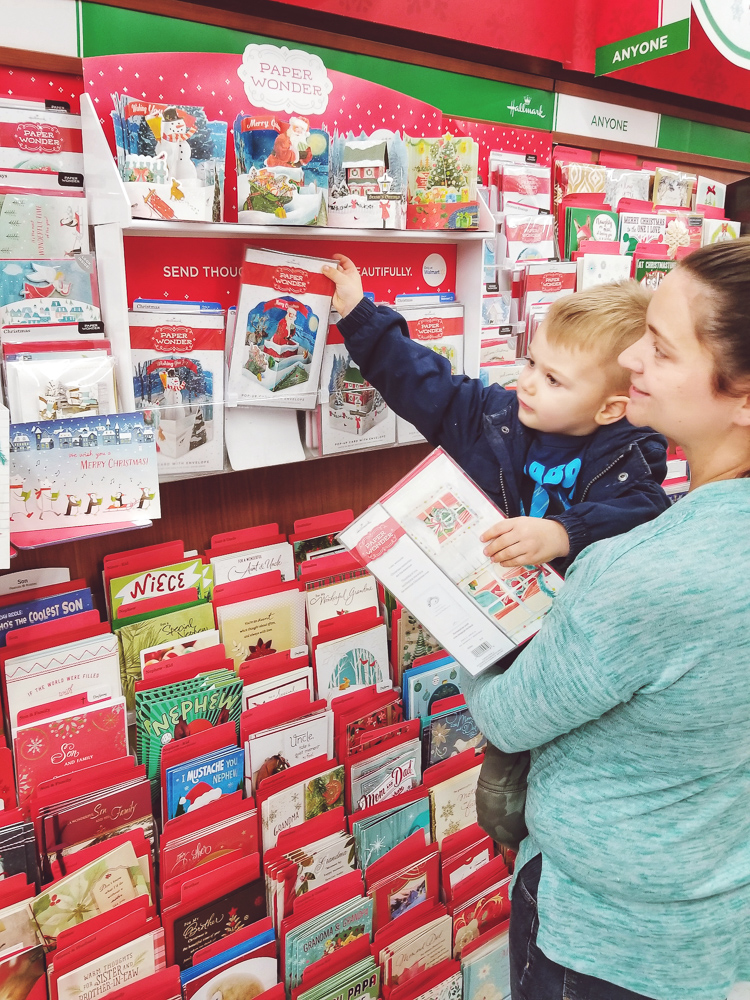 Hallmark Holiday Cards_toddler in Walmart with cards