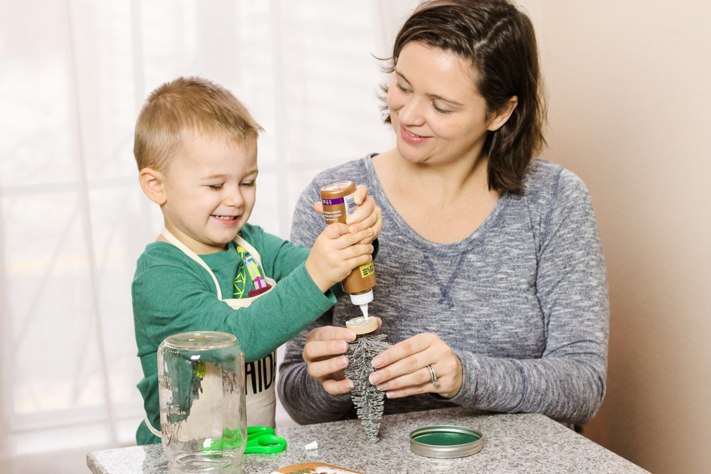 Toddler Christmas Ornaments_toddler happily glues christmas tree