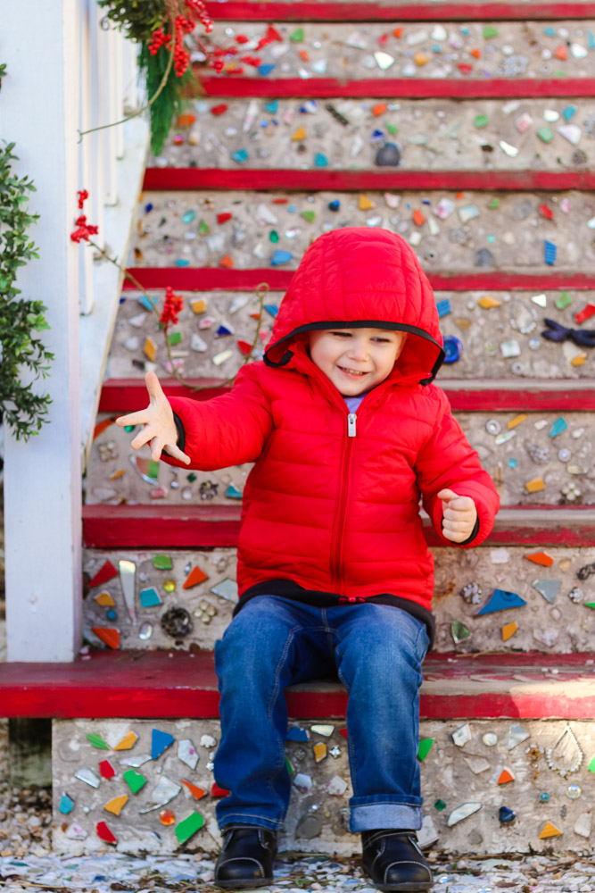 The Best toddler boy jeans featured by top DC mommy blog, Baby Castan on Board: image of a toddler boy wearing Old Navy toddler boy jeans and a red puffer hooded jacket