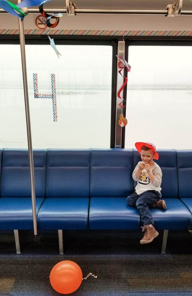 How to Plan a Birthday Party at the Airport for Your Child by popular DC mommy blog, Baby Castan on Board: image of a little boy riding on a airport shuttle.