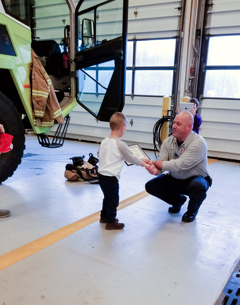 How to Plan a Birthday Party at the Airport for Your Child by popular DC mommy blog, Baby Castan on Board: image of a little boy at an airport fire station.