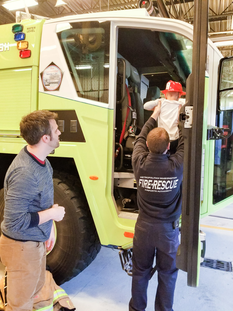 How to Plan a Birthday Party at the Airport for Your Child by popular DC mommy blog, Baby Castan on Board: image of a little boy getting in a airport firetruck.