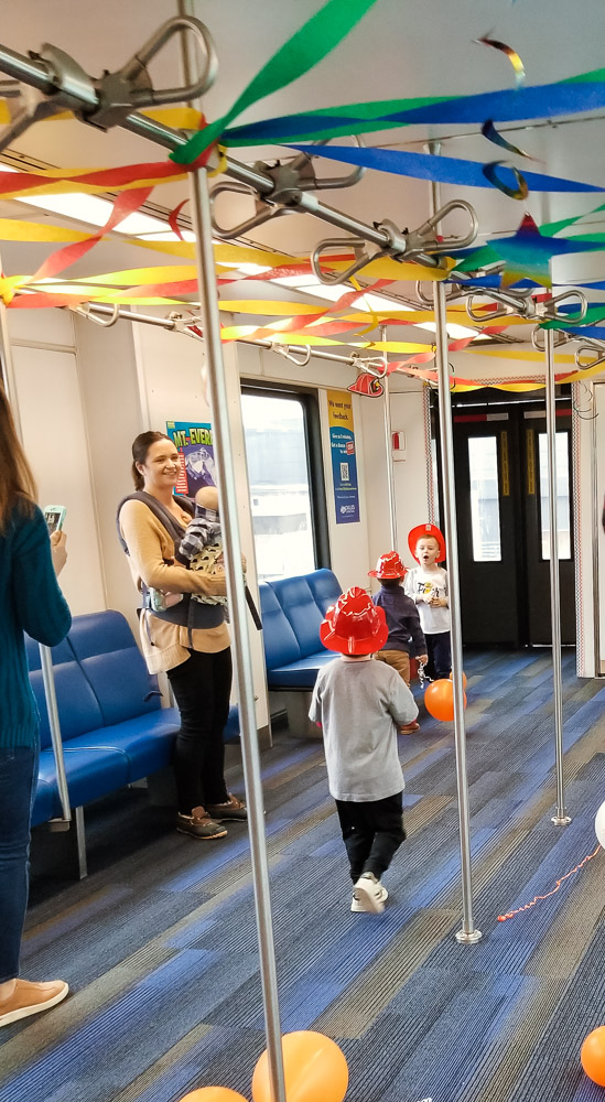 How to Plan a Birthday Party at the Airport for Your Child by popular DC mommy blog, Baby Castan on Board: image of kids riding on a airport shuttle decorated with crepe paper and balloons.