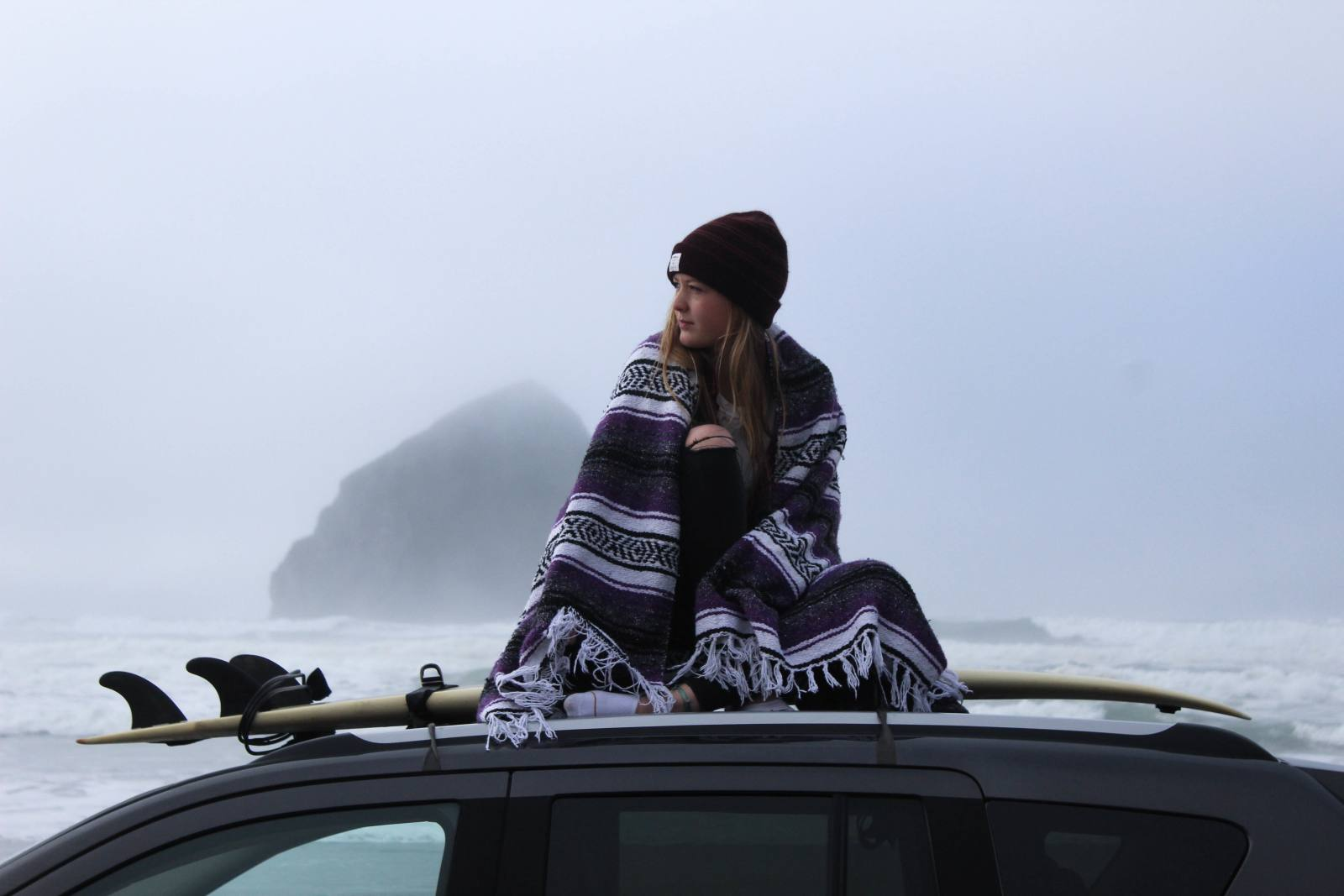 woman sitting on car while wearing hat and shawl