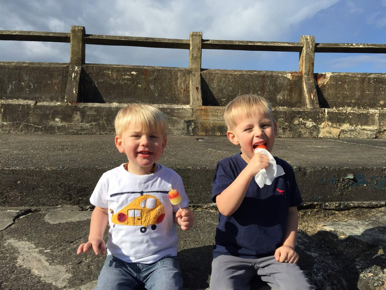two boys sit in tynemouth swimming pool and eat ice lollies in the sun