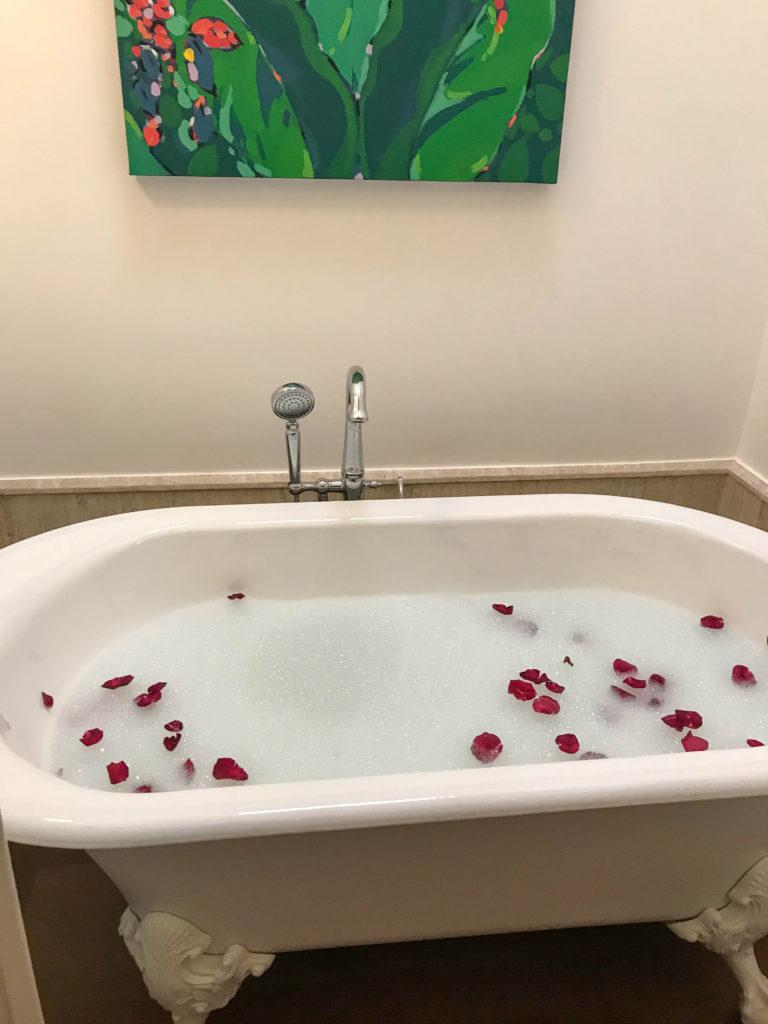 clawfoot bathtub with bubbles and rose petals at Casa Antillana