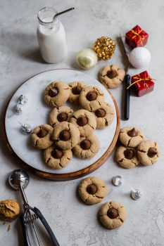 Peanut Butter Blossoms on a round serving tray with milk and Hershey's kisses.