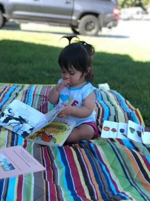 Tilly reading Click Clack Moo.