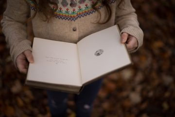 Child in a sweater holding a book outside