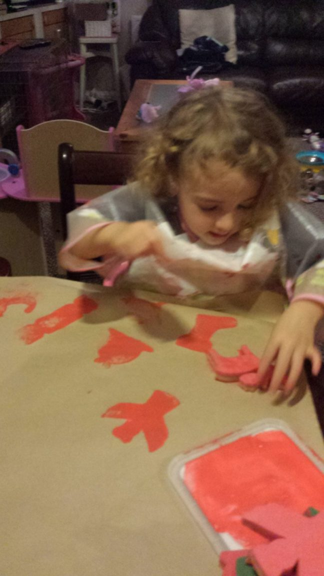 Sponge painting onto brown craft paper with christmas shapes