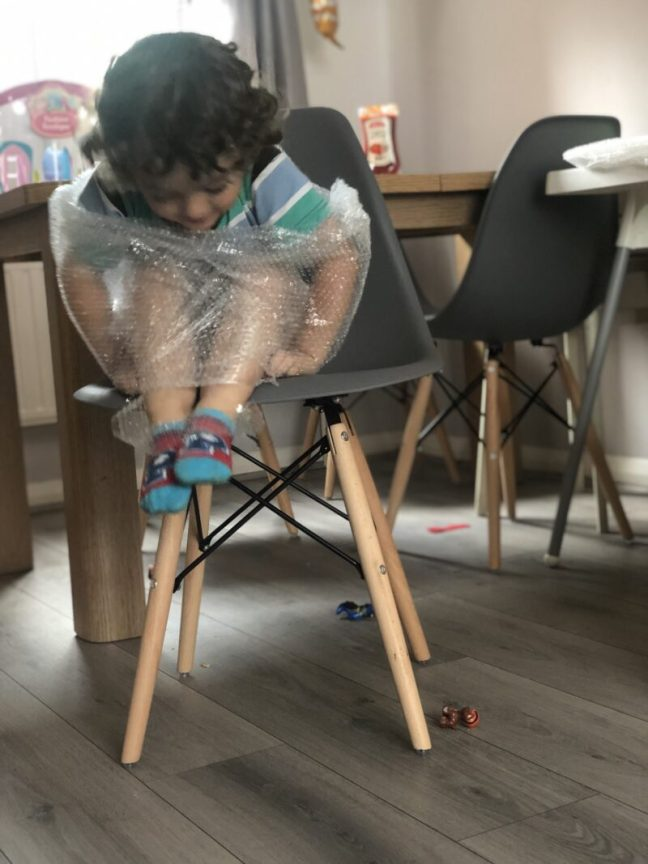 A toddler boy playing with bubble wrap