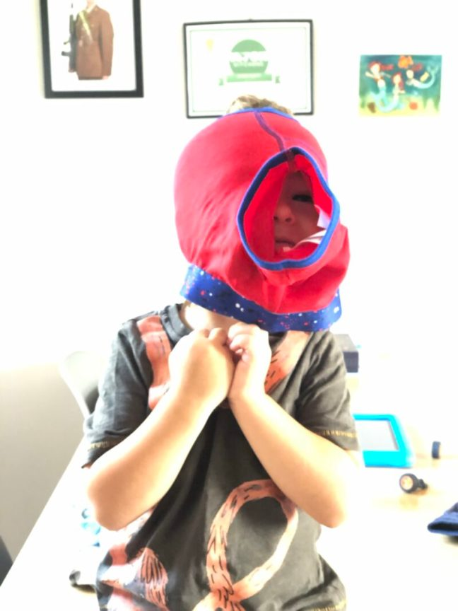 A toddler boy with a pair of boxer shorts on his head