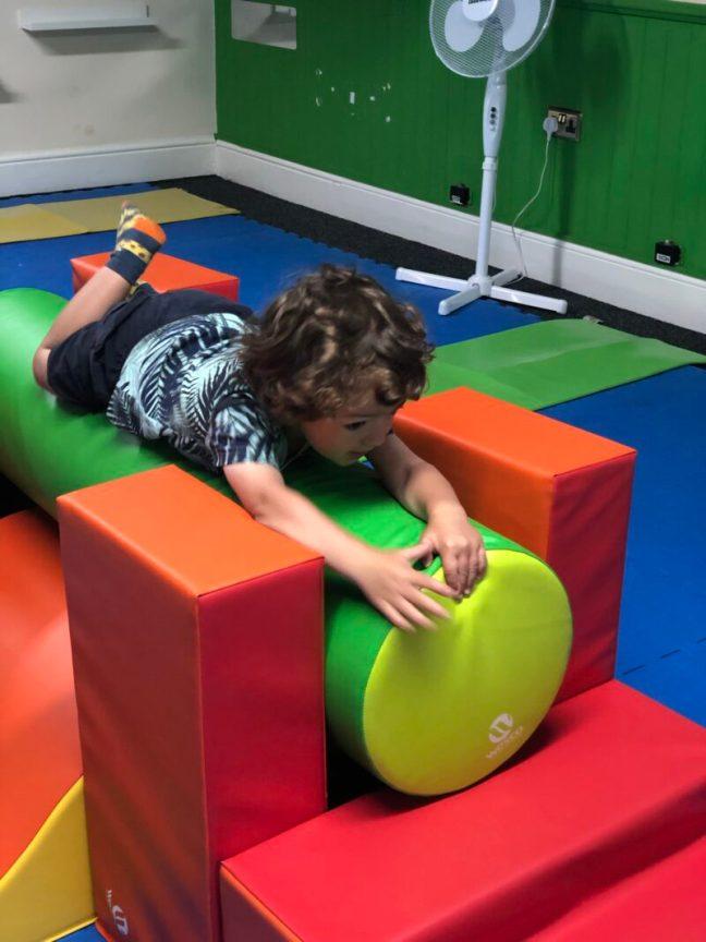 A toddler boy climbing on foam shapes at toddler sensory class