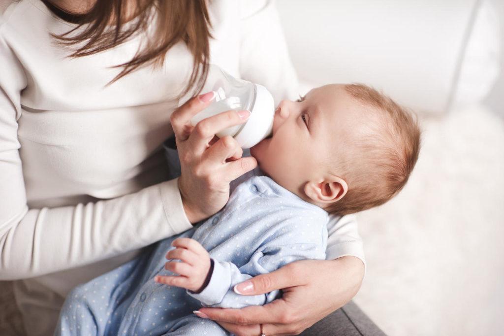 mujer alimentando a su bebé con un biberón