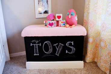 Peyton's toy box was customized by adding crown moulding and chalkboard paint. She also made the top into a padded seat.