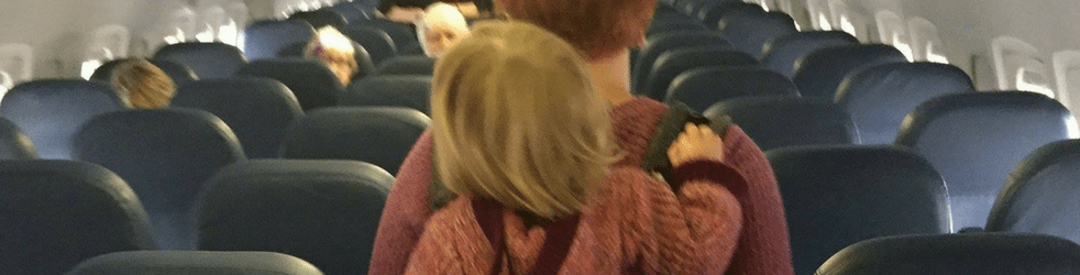Back of a woman with her toddler in a carrier on her back walking down the aisle of an airplane with the backs of blue seats on both sides of the aisle.