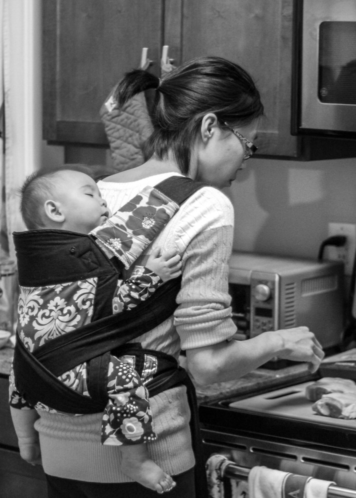 """[Black and white photograph of aTaiwanese American woman with her back to the viewer, in her kitchen preparing food while wearing a sleeping infant on her back in a black, gray, and white damask-patterned bei dai/meh dai. The shoulder straps make an """"x"""" across the infant's bottom and go back under the legs to tie off in front.]"""