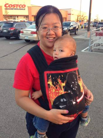 Photograph of a Chinese woman smiling at the camera in a parking lot wearing a baby in the front using a black bei dai/meh dai carrier featuring Darth Vadar on the panel.