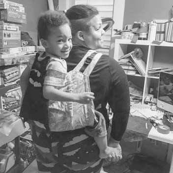 [Collage of four square black and white photographs of a smiling black woman wearing a child on her back in a buckle-style onbuhimo; they are in a room with a desk, books, and board games. Top left shows the back with the child's batman cape covering the back of the carrier. Top right shows the front with both child and mother smiling, you can see the shoulder straps and chest buckle. Bottom left shows the front with both child and mother smiling with mother's left hand on her hip. Bottom right shows the back with child turned to smile at the camera; the carrier hood and part of the back panel is visible.]