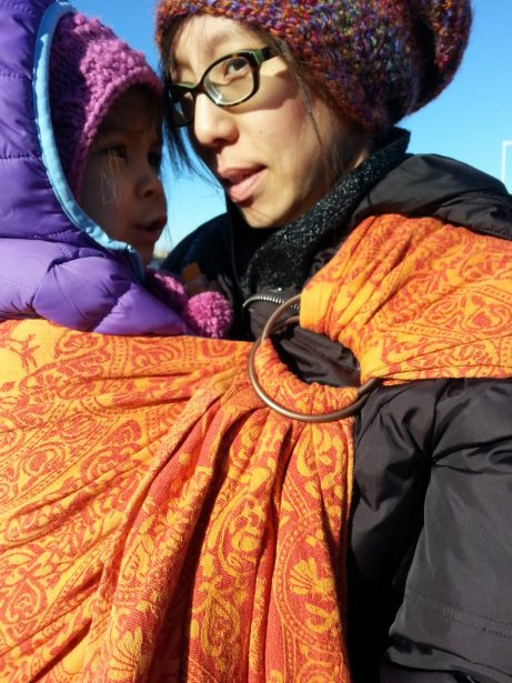 Image of a light tan skin bespectacled Asian woman in a dark down jacket wearing a toddler in a purple down jacket on her hip using a red and orange patterned ring sling baby carrier with bronze rings with a floating shoulder. They are outside in the frigid cold air with blue skies above.