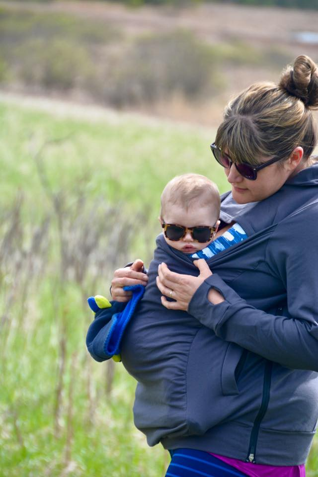 (Image of a white brunette woman carrying a 5 month old blonde baby boy in a blue Ergo. They are both covered by a gray Boba sweatshirt with a cutout for the baby's head.)