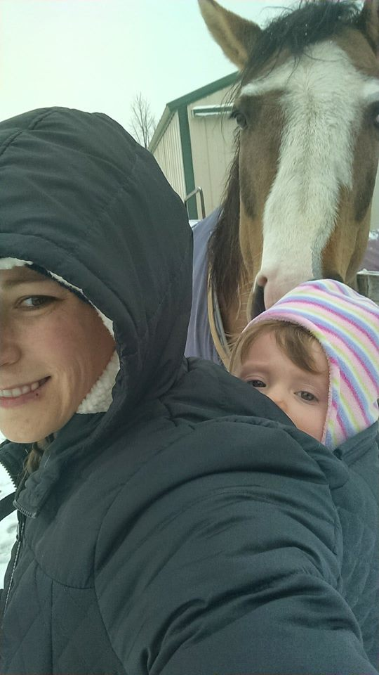 (image of a white woman with a white girl on her back, the woman has a black hooded coat on with a hole for the girls bag to come through. There is a horse photo bombing in the background)