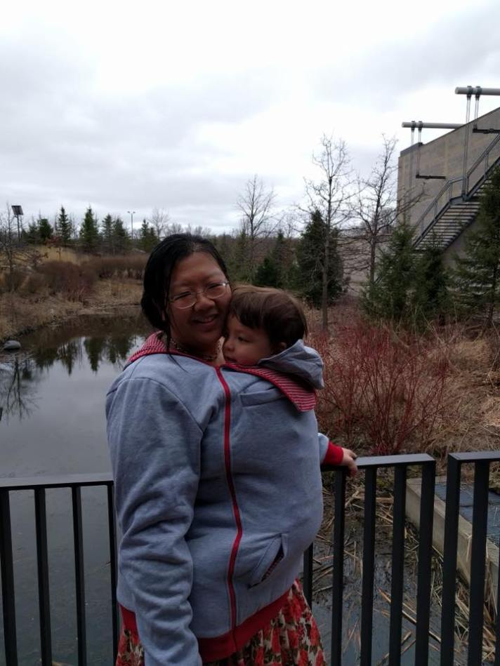 [image of an East Asian woman with glasses in a gray and red babywearing sweatshirt. A mixed-race boy's head pokes out of the sweatshirt in front of her face. She is holding onto a black railing and a pond and fall scenery is in the background.]