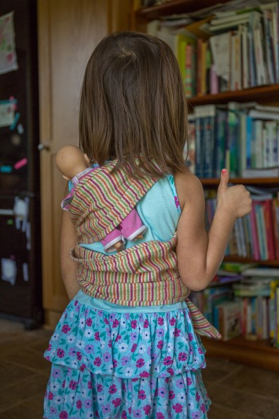 Image from the back of a tan skin light brown haired child wearing a doll on her back in a multi-colored striped piece of fabric that is being used as a doll wrap carrier. Doll is a little askew on child's back. Child has a thumbs up. In the background is a bookshelf full of books.