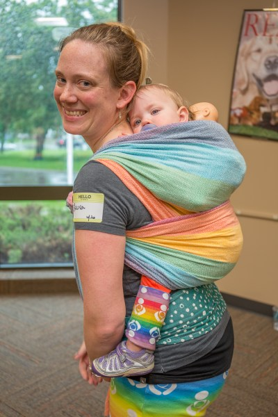 [Image of a smiling volunteer who is wearing a toddler on her back in a bright rainbow striped woven wrap. The toddler is wearing a baby doll on her back too which is wrapped inside the woven wrap.]
