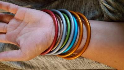 Image of different colors of aluminum rings made for safe babywearing on a white woman's wrist