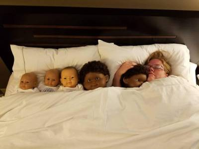 Image of a redheaded white woman snuggling several demo babies with various skin tones.