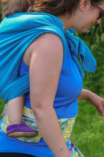 Image from the side of a white woman with dark brown hair and sunglasses wearing a toddler on her back in a turquoise woven wrap that matches her tank top. At her waist is a yellow and green pouch with a zipper for carrying little things on the go.