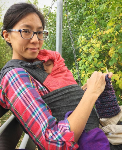 [Image of a tan skin bespectacled tired smiling Asian woman wearing her favorite rainbow-plaid top. She's sitting on a rocking bench outside at the park in the cloudy afternoon breeze while wearing a sleeping toddler on her front in a black chambray and pinkish-orange-ish linen meh dai baby carrier. In her hands she has knitting needles and purple yarn in the works. In her lap is a natural white cotton drawstring bag holding the skein of yarn. Behind her are green leaves turning yellow with the changing season.]