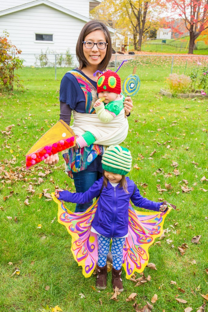 A smiling tan skin bespectacled Asian woman wearing a colorful flowy top and jeans has a baby worn on her front in an ecru woven wrap carrier in a torso front carry to mimic an egg. The baby is dressed up as a caterpillar in a green outfit and Mama-crocheted red hat with felt eyes and nose sewn on with purple pipe cleaners for antennae. Next to the baby is a child with colorful wings worn on the back and a mama-knit two-toned green hat that resembles a caterpillar. In Mama's hands are two food props she painted on cardboard to mimic that from the Eric Carle story. One is a pie with pom poms for the cherries and the other is a swirly lollipop.