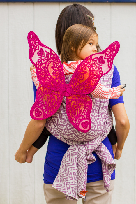 Back view of a toddler worn on the back of a Mama in a lilac and ecru woven wrap carrier that's tied under the toddler's bum. Toddler has on large pink sparkly wings and has arms out over the top of the carrier. Mama's hands are playing with toddler's bare feet.