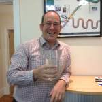 Picture showing Eastbourne Chiropractor James Revell Doctor of Chiropractic, LRCC, MSc (Chiropractic Sciences), BSc (Chiropractic Sciences) with a large glass of water next to his chiropractic notes