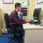 Image shows Eastbourne Chiropractor Mykel Mason demonstrating a slumping position at his desk, with his shoulders rounding forwards. Follow our wellness tips to avoid this.