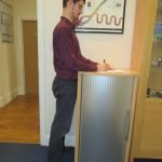 Image shows Eastbourne Chiropractor Mykel Mason standing at work which is one of our wellness tips