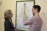 Image shows Eastbourne Chiropractor Mykel Mason looking at a poster of the nervous system.