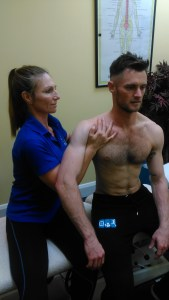 Image shows sports massage therapist Kim Brown working on the shoulder of colleague Oliver Ody to accompany her blog on shoulder injuries