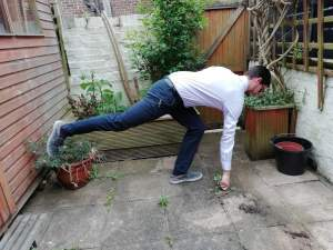 The picture demonstrates a man bending over with his back leg out whilst he reaches down and pulls on a weed. To accompany the blog on gardening by Eastbourne Chiropractor Mykel Mason