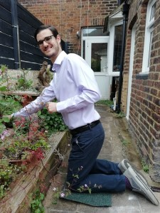 A picture of man kneeling in front of weeds to be down at a lower level to accompany the blog on gardening by Eastbourne Chiropractor Mykel Mason