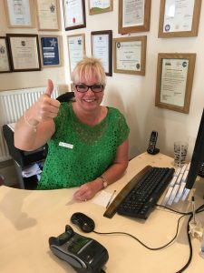 Image shows clinic assistant at Lushington Chiropractic, seated behind the reception desk giving a thumbs up sign. To accompany her blog on frequently asked questions.